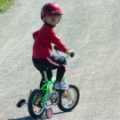 Helmeted_boy_on_training_wheels
